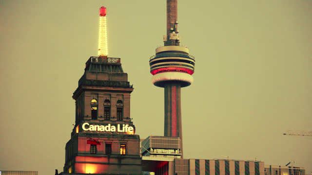 canada life building and the cn tower on july 29, 2017; in toronto, ontario, canada. the canada life building has a weather beacon on top. the cn... - 社会史点の映像素材/bロール