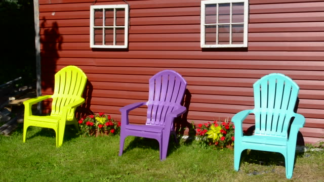 canada peggy's cove nova scotia barn with colorful adirondack chairs with flowers - アディロンダックチェア点の映像素材/bロール