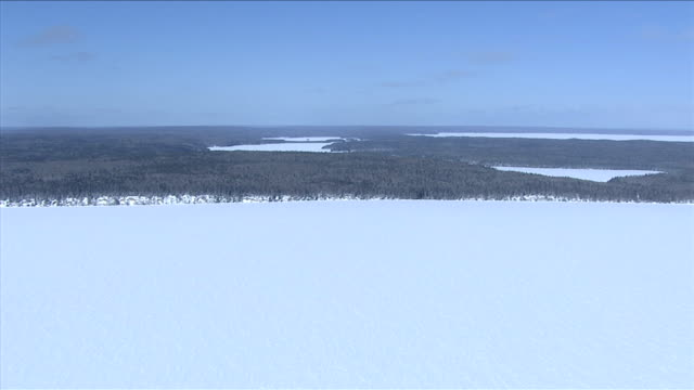 Canada's boreal forest covers land between frozen rivers and lakes. Available in HD.