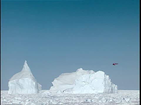 vidéos et rushes de ws canadian coast guard helicopter checking iceberg in thick pack ice, labrador sea, canada - iceberg bloc de glace
