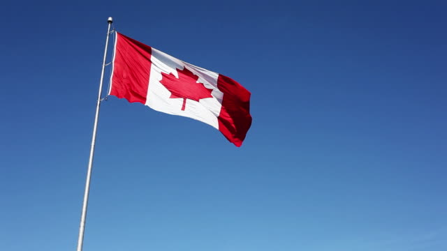 Canadian Flag Against Clear Blue Sky