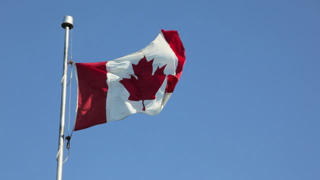 Canadian Flag Floating and Flying on Blue Sky