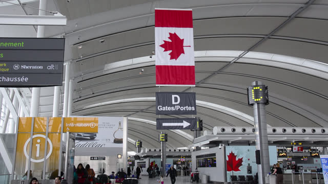vídeos de stock e filmes b-roll de canadian flag in the pearson airport where people go out and about their lives seen on february 12, 2016; in toronto, ontario, canada. the toronto... - bandeira do canadá