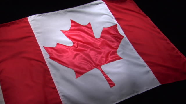 cu, pan, canadian flag on black background - canada flag stock videos & royalty-free footage