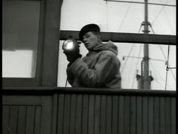 vídeos de stock, filmes e b-roll de canadian merchant ships signaling w/ light . sailor signaling w/ light. aerial: freighter carrying airplane supplies at sea. britain flag raising on... - oceano atlântico