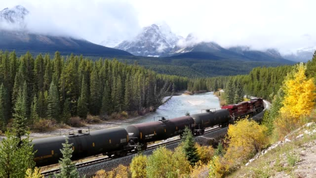 canadian pacific railway long freight passing in autumn valley on bow river at morant's curve - traditionally canadian stock videos & royalty-free footage