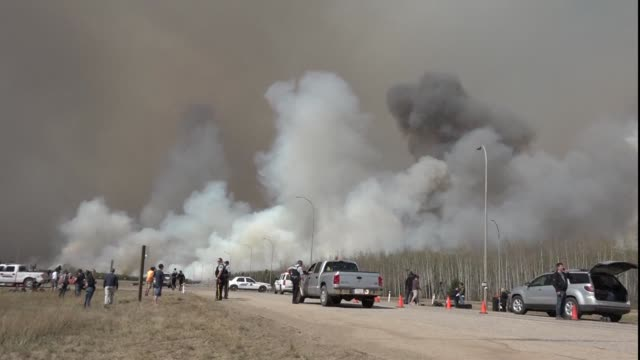 Canadian police lead convoys of cars through the burning ghost town of Fort McMurray in a risky operation to get thousands of people to safety on the...