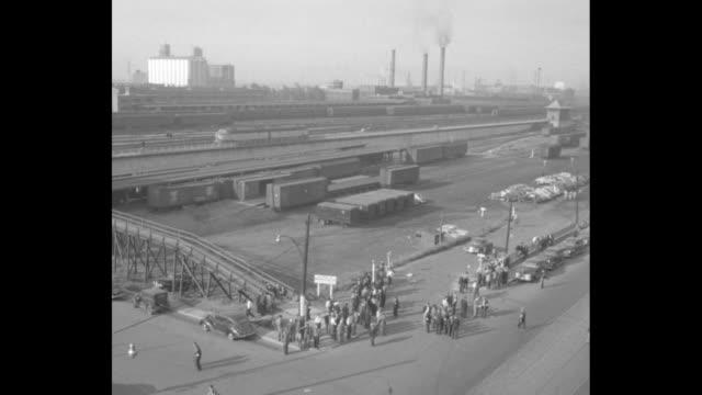 Canadian railway strike /crowd of men at rail yards / CU man with armband saying 'picket' / aerials rail yards with picketers / large group picketers...
