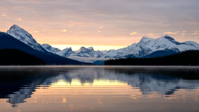 canadian rockies with foggy reflection on maligne lake and colorful sky in morning at jasper national park, canada - jasper national park stock videos & royalty-free footage