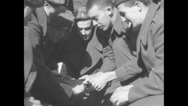canadian soldier lights another's cigarette / soldier plays cards / cards and money on ground as soldiers play / soldiers with cards / vs soldiers... - railings stock videos & royalty-free footage