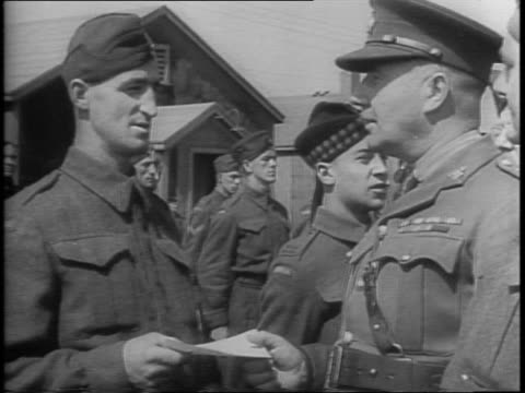 Canadian soldiers voluntarily return to mines / Canadian soldiers lining up / closeup of soldier getting furlough notice from officer / soldier at...