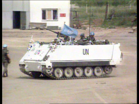 sarajevo aid itn bosnia sarajevo apcs towards along lms un apc with soldier at machine gun towards tlms un apc by buildings at airport along pull out... - sarajevo stock-videos und b-roll-filmmaterial