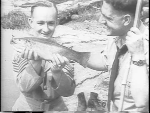 vídeos de stock, filmes e b-roll de canadian uniformed man fishing at a wooded shoreline / serviceman lounging with pole outstretched, hat, boots and jacket off / with magazine with... - publicação