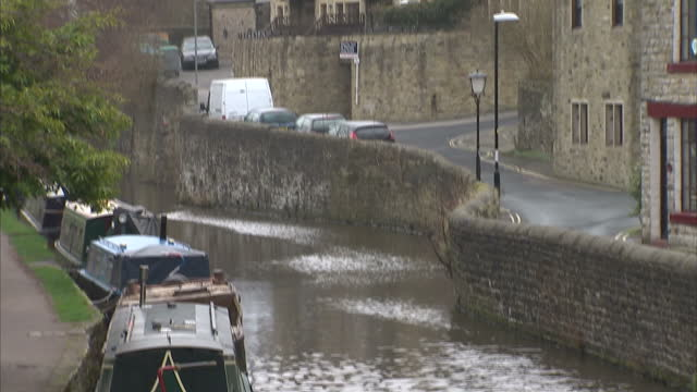 canal and canal boats with church on march 16, 2014 in skipton, england. - skipton stock videos & royalty-free footage