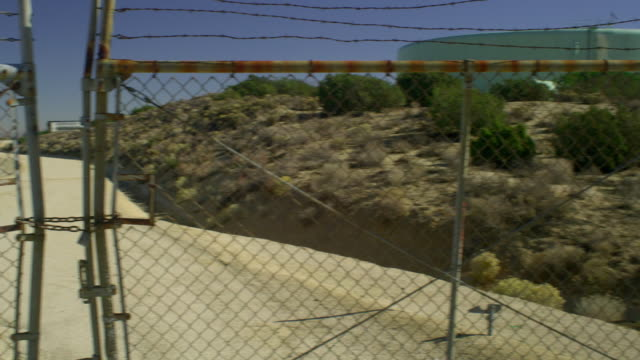 ms pan ws canal behind chain link fence and highway in desert landscape, palmdale, california, usa - palmdale stock videos and b-roll footage