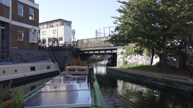 a canal boat travelling along the regent's canal in east london. - east london stock videos and b-roll footage