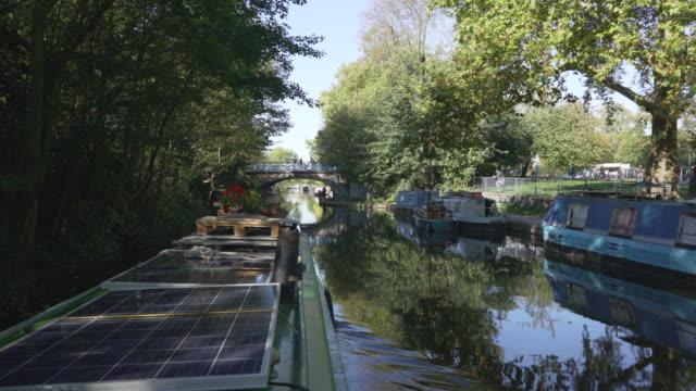 vídeos de stock e filmes b-roll de a canal boat travelling along the regent's canal past victoria park - barco casa