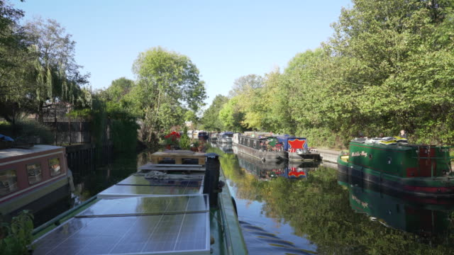 a canal boat travelling along the regent's canal past victoria park - canal stock videos & royalty-free footage