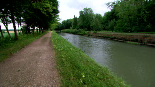 a canal flows alongside a dirt path. - irrigation equipment stock videos & royalty-free footage
