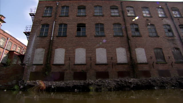 A canal flows alongside an old brick mill building. Available in HD.