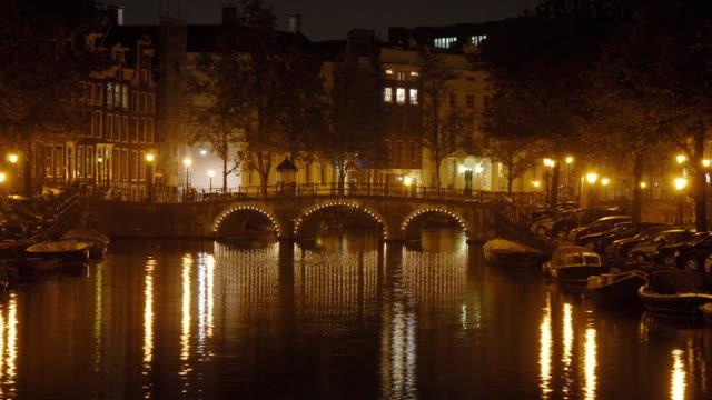 t/l, ws, canal illuminated at night, amsterdam, north holland, netherlands - tonad bild bildbanksvideor och videomaterial från bakom kulisserna