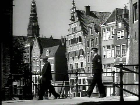 vídeos de stock, filmes e b-roll de canal in amsterdam boat going under bridge buildings ws dutch architecture man on bridge bicyclist ws women spraying sweeping steps to house ms woman... - 1947