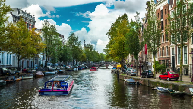 canal in amsterdam with tourboat - 4k cityscapes, landscapes & establishers - canal stock videos & royalty-free footage