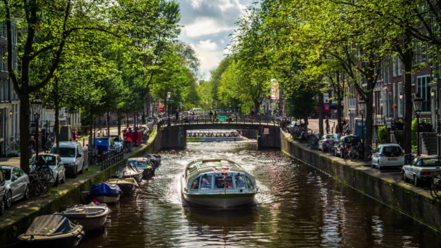 canal in amsterdam with tourboat - canal stock videos & royalty-free footage