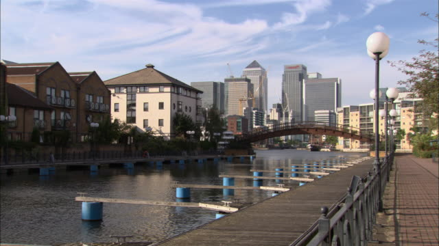 canal on river thames with arch bridge crossing over and promenade running alongside / london docklands and canary wharf in distance / london, england - flussufer stock-videos und b-roll-filmmaterial