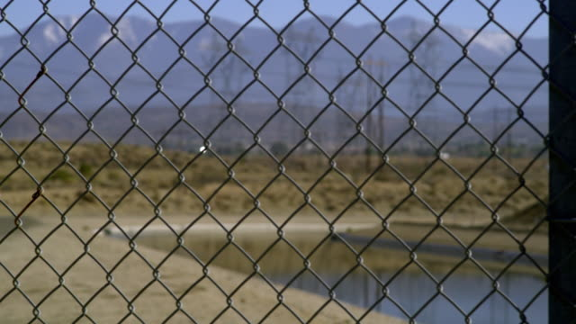 ms r/f canal seen through chain link fence, electricity pylons and mountains in background, palmdale, california, usa - palmdale stock videos and b-roll footage