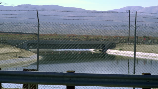 ms canal seen through chain link fence, highway and hills in background, palmdale, california, usa - palmdale stock videos and b-roll footage