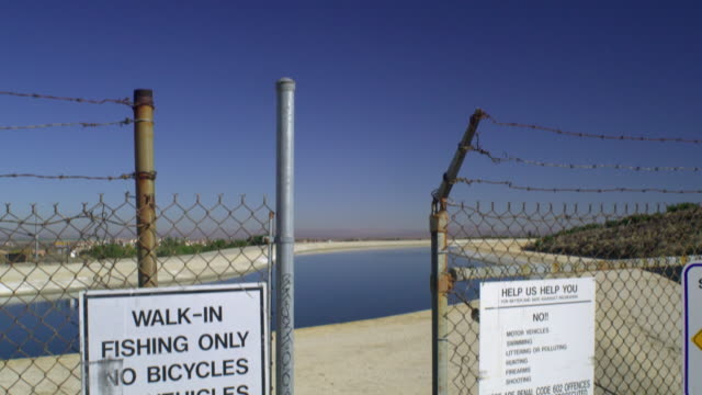 cu td canal seen through chain link fence, palmdale, california, usa - palmdale stock videos and b-roll footage