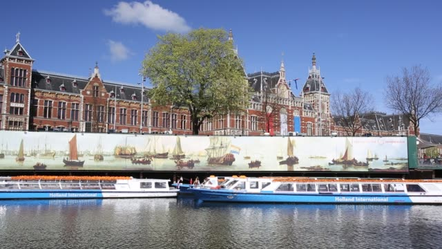 canal tour boats infront of amsterdams central station, netherlands - in front of stock videos & royalty-free footage