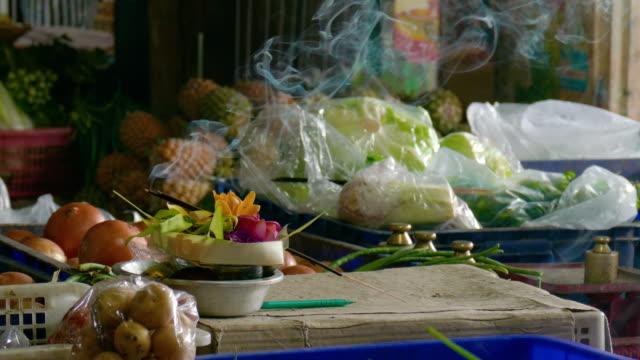 MS Canang sari with burning incense at market, Ubud, Bali, Indonesia