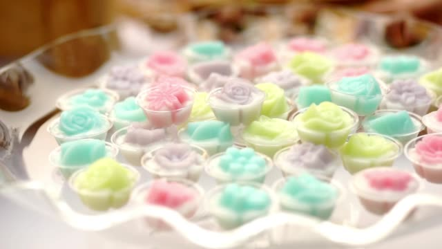 canape of thai traditional dessert with multicolored of mini coconut milk jelly flower shape on plate for self-service at outdoor wedding events. - sweet food stock videos & royalty-free footage