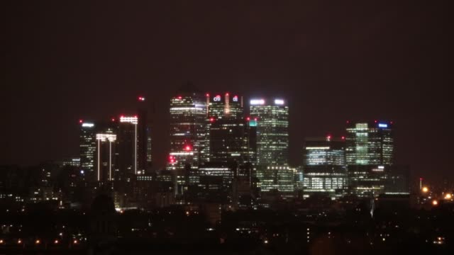 canary wharf stand illuminated at night in london, united kingdom on monday, january 12 wider shot of canary wharf, timelapse of dawn breaking over... - ナイトイン点の映像素材/bロール