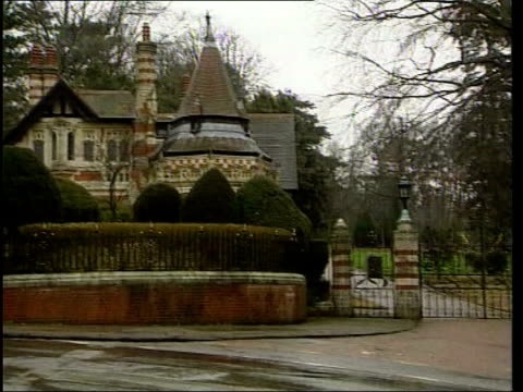 cancer scare lib oxfordshire entrance to home of harrison where he was stabbed by an intruder pan police officer and car outside gates - george harrison video stock e b–roll