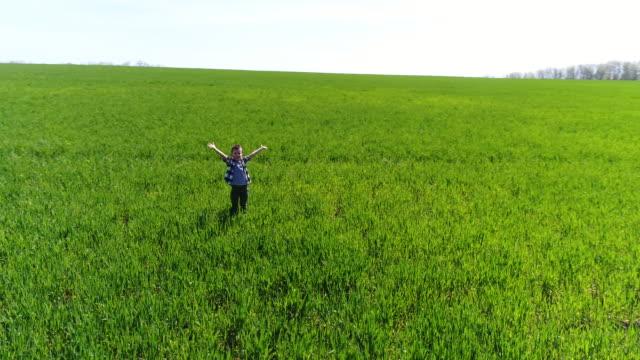 vídeos y material grabado en eventos de stock de chico sincero levantó las manos en campo verde; vista aérea - alcanzar