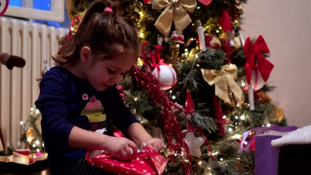candid emotion of little girl unwrapping christmas present - christmas gift stock videos & royalty-free footage