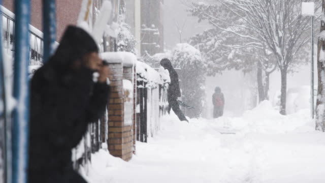 Candid establishing shot of unrecognizable people in a New York City snow storm