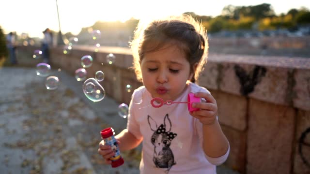 candid girl playing with a bubble wand - soap sud video stock e b–roll