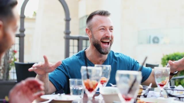 vídeos y material grabado en eventos de stock de momentos felices y sinceros con amigos en un brunch de fin de semana en un restaurante en la azotea - multi ethnic group