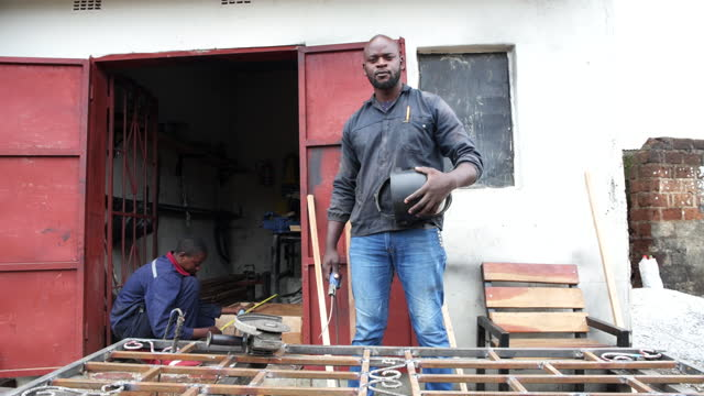 candid portrait african male welder outside fabrication workshop - one mid adult man only stock videos & royalty-free footage
