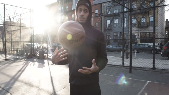 Candid portrait of a real person playing basketball at a neighborhood court in Brooklyn, NYC - 4k