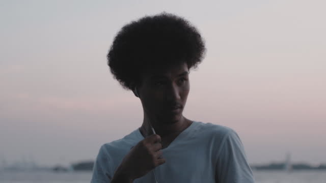 vídeos de stock, filmes e b-roll de a candid portrait of a young, mixed race man along the coast of new york's hudson river. - fones de ouvido intracanal