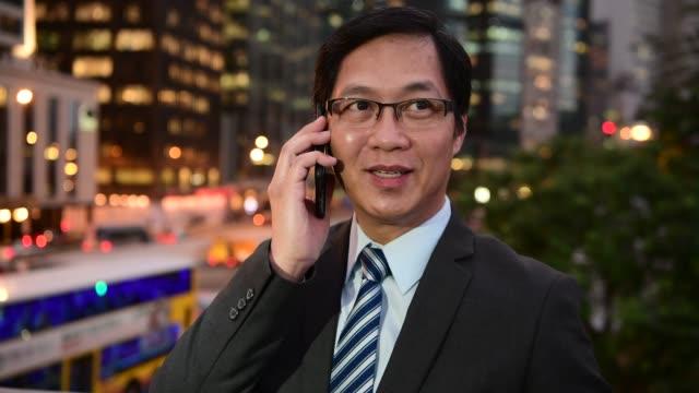 中國商人晚上在城市里打電話的坦誠畫像 - looking away 個影片檔及 b 捲影像