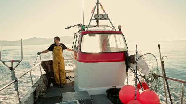 candid portrait of fisherman motoring in mediterranean sea - fisherman stock videos & royalty-free footage