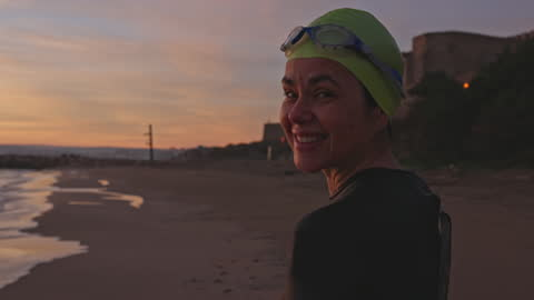 candid portrait of mature female swimmer on beach at dawn - swimming goggles stock videos & royalty-free footage