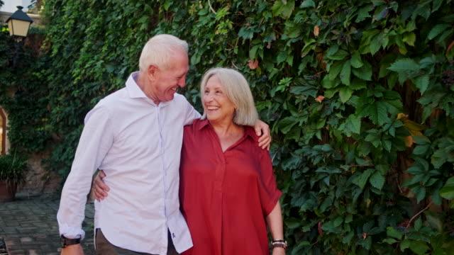 屋外を歩く笑顔のシニアカップルの率直な肖像画 - ペア点の映像素材/bロール