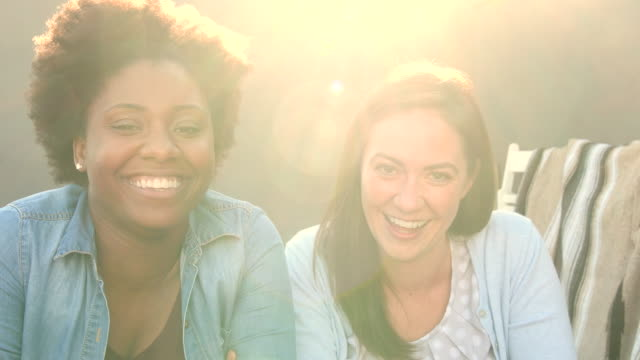 candid portrait of two women laughing together, lens flare - amicizia tra donne video stock e b–roll